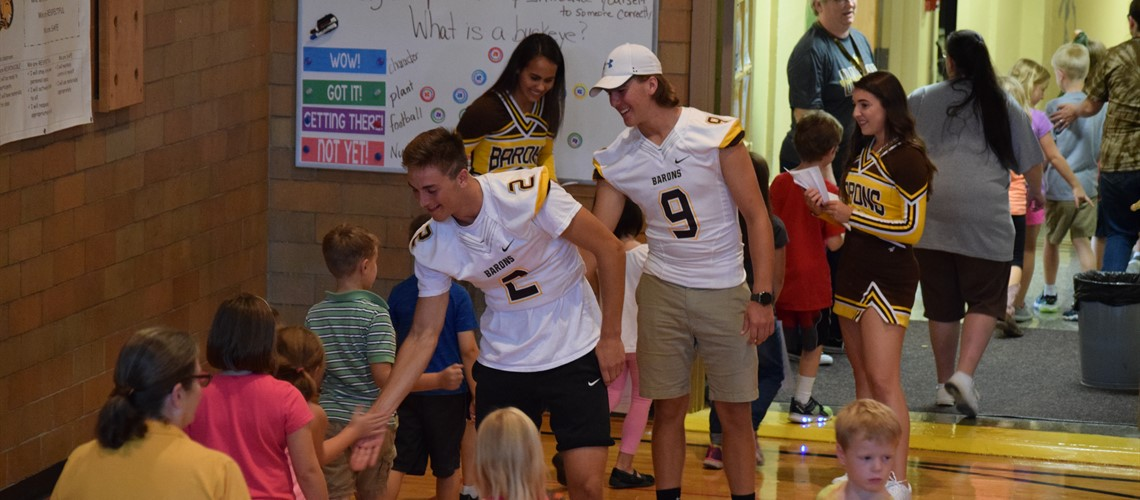 BV football players with elementary students